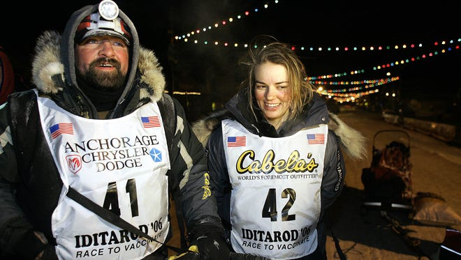 FILE - In this Saturday, March 18, 2006, file photo, Tim Osmar of Ninilchik, Alaska, left, who drove his dog team in front of  Rachael Scdoris, right, as her visual interpreter during the Iditarod Trial Sled Dog Race, stands with Scdoris at the finish in Nome, Alaska. Scdoris completed the race, placing 57th among 72 finishing teams, and the 10-year anniversary of her becoming the first legally blind musher to finish the Iditarod is just three months away.
