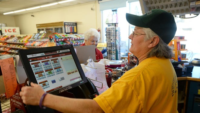 Debbie Dean sells lottery tickets on Tuesday at Schulte's convenience store.