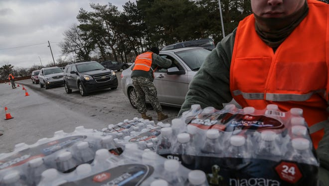 U.S. Army National Guard 125th Infantry Battalion members from Michigan hand out water on Monday January 18, 2016 at Flint Fire Department Station 1 to help residents dealing with lead in their drinking water during the Flint water crisis.