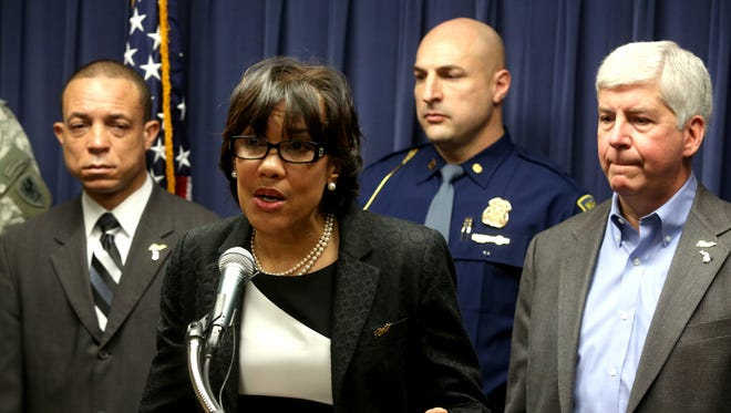 Flint Mayor Karen Weaver talks to the media during a news conference Wednesday, Jan. 27, 2016, as Gov. Rick Snyder (far right) listens to her at the City of Flint Municipal Center.