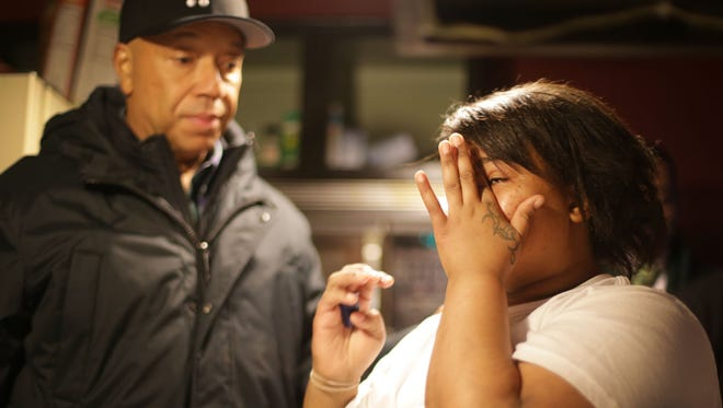 Nakeyja Cade, 24, Flint resident and mother of three is emotional as she speaks with Russell Simmons after he delivers cases of water to RushCard customers in the city.