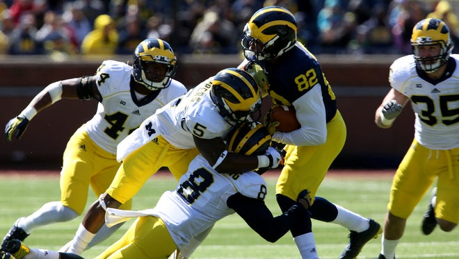 Amara Darboh (82) gets stopped by Jabrill Peppers (5) and Channing Stribling after catching the ball during the Michigan spring football game at Michigan Stadium in Ann Arbor on April 4, 2015.