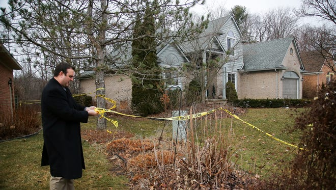 Novi police detective secures the police tape around this home in the 23000 block of Mystic Forest Drive where five Mexican immigrants died in a house fire.
