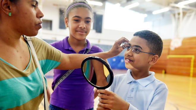 Randy Espinal, 9, tries on eyeglass frames with help from his mother Jasmine Vargas and sister Diana Espinal, 12, during a free eye-screening session for York City School District students. The four-hour session, hosted by Family First Health and Envolve, provided screenings for 48 kids, 23 of whom needed and received free glasses.