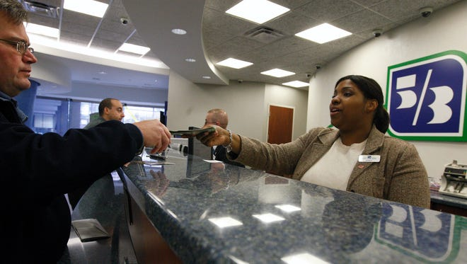 Customer Service Representative Janelle Stewart with Fifth Third Bank helps David Owens with a transaction at the Fifth Third Bank on Fountain Square, Downtown.