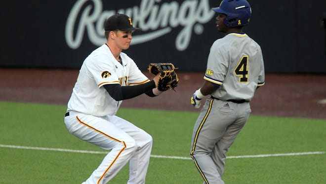 Iowa first baseman Tyler Peyton tags out Michigan's Ako Thomas during Friday's series opener at Duane Banks Field.
