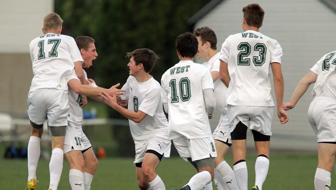 West High teammates celebrate with Jackson Nasby after his goal against Linn-Mar on Tuesday, April 26, 2016.