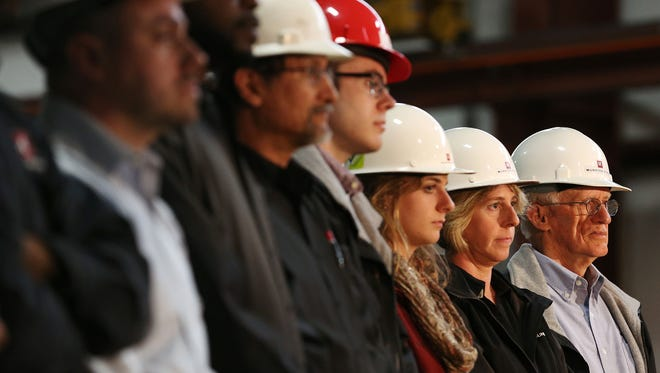 Munster Steel employees stand behind Democratic presidential front-runner Hillary Clinton as she speaks at their workplace in Hammond, Ind., Tuesday, April 26, 2016.