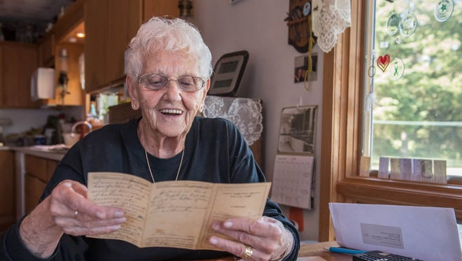 Virginia Moody, who attended Fremont Elementary School in the 1930s, looks back at old report cards. Decades passed before Moody stepped back into the school last week, days before it's set to close.