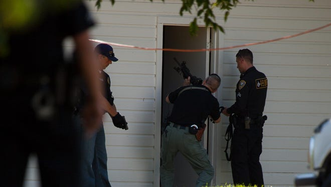 Police follow a K-9 unit into a shed outside Havaii Akane's fiance's apartment, on the 600 block of 27th Street North after his escape from custody in 2010. Akane, a registered violent offender, escaped during a transfer at the Great Falls Pre-release Center.