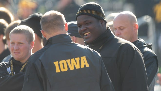Juan Harris stands on the sidelines with Iowa assistant Seth Wallace prior to the Hawkeyes' game against Indiana at Kinnick Stadium on Monday, Oct. 13, 2014.  David Scrivner / Iowa City Press-Citizen