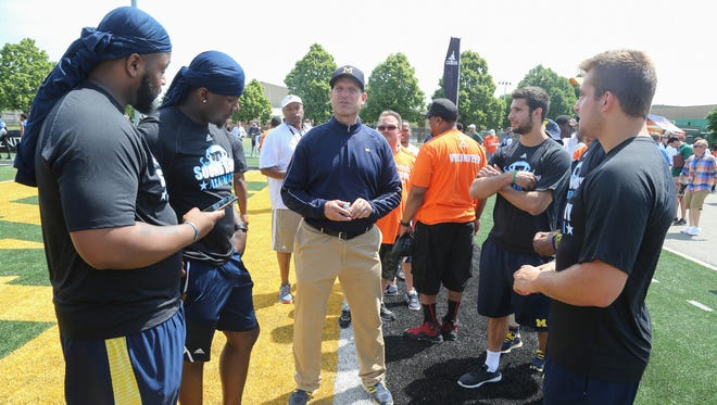 Michigan football coach Jim Harbaugh talks to some of his players during the Sound Mind Sound Body football camp at Wayne State on June 10, 2016.