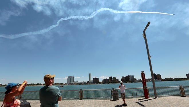 Spectators take photos as they follow the white line of smoke from the air show, staged by the Tuskegee Airmen National Historical Museum.