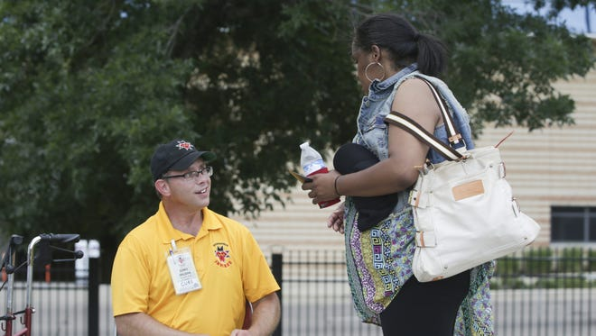 Cory Wilson, a security guard, gives Monica Lawrence a raffle ticket at Victory Field on June 26, 2016.