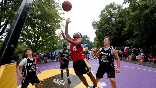 Darien Summers, with the Bucket Squad, takes a shot while surrounded by Perez Rat Pack players in the 14 and under boy's championship game for the Hoopla basketball tournament outside the Oregon State Capitol in Salem on Sunday, Aug. 7, 2016.