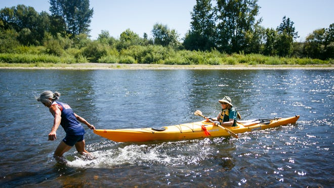 Lisa Lum helps pull Lilli Gloor's kayak to shore as their Paddle Oregon pod takes a break on Tuesday, Aug. 16, 2016. This was the first year on the five-day river trip for both Lum and Gloor.