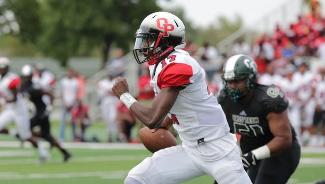 Oak Park's quarterback Dwan Mathis runs the ball by Cass Tech's Eric Smith in the second half of the Detroit Prep KickOff Classic, Aug. 28, 2016 at Wayne State University's Tom Adams football field.
