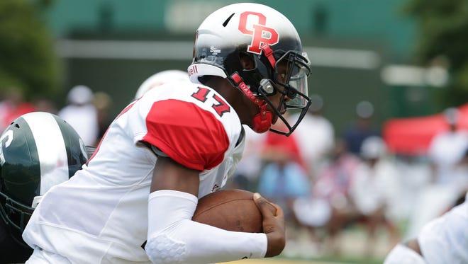 Oak Park's Dwan Mathis runs the ball against Cass Tech in the Detroit Prep Kickoff Classic, Aug. 28, 2016 at Wayne State University's Tom Adams football field.