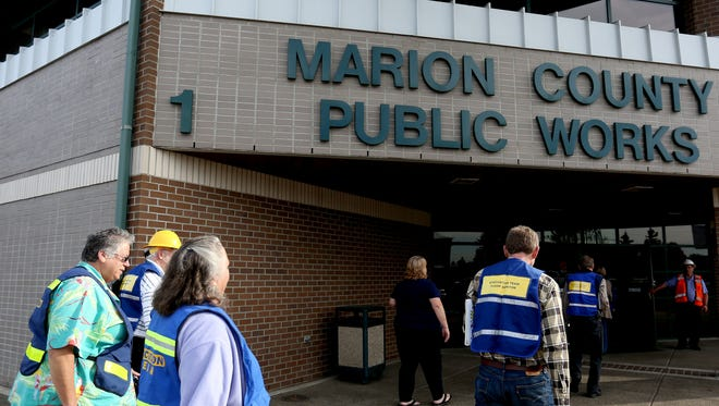 Employees re-enter the building after an earthquake evacuation drill, part of an international effort to promote earthquake drills, at Marion County Public Works in Salem on Thursday, Oct. 15, 2015.