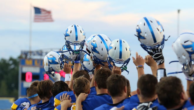 Mukwonago High School football players raise their helmets at the end of the National Anthem on Sept. 9. Mukwonago faced Muskego, winning 21-0.
