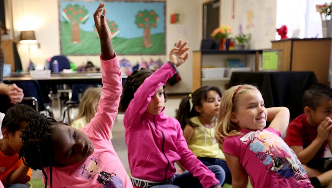 Students raise their hands during class at Highland Elementary School in Salem.
