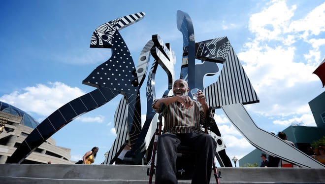 """Detroit artist Charles McGee is photographed in front of his monumental new outdoor sculpture """"United We Stand,"""" at the Charles H. Wright Museum of African American History on Saturday, July 13, 2016 in Detroit. It is first in the Wright Museum's art series on the 1967 civil unrest."""