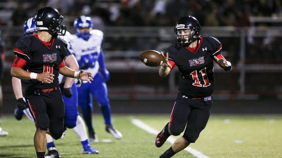 North Salem quarterback Hunter Sullivan (11) tosses the ball to running back Alex Vasquez (8) in the second half of the season opening-game against McNary on Friday, Sept. 2, 2016, at North Salem High School. McNary won the match-up 38-35.