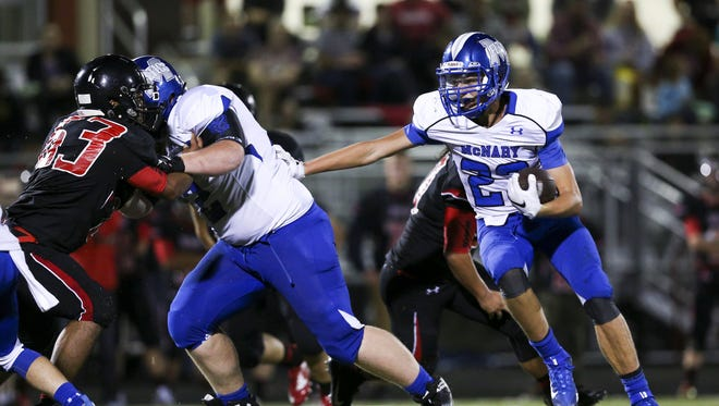 McNary junior running back Lucas Garvey (23) tucks in the ball and looks for a way through North Salem's defense in the season opening-game on Friday, Sept. 2, 2016, at North Salem High School. McNary won the match-up 38-35.
