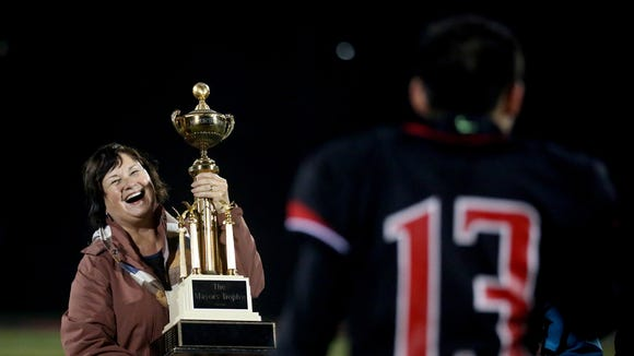 Mayor Anna Peterson presents the Mayor's Trophy to North Salem following the South Salem vs. North Salem football game at North Salem High School on Friday, Oct. 7, 2016. North Salem won the game 23-22.