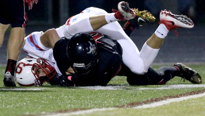 South Salem's Gavin Baughman (3) and North Salem's Junior Sandoval (9) fight for the ball in the second half of the South Salem vs. North Salem football game at North Salem High School on Friday, Oct. 7, 2016. Sandoval came out with an interception. North Salem won the game 23-22.