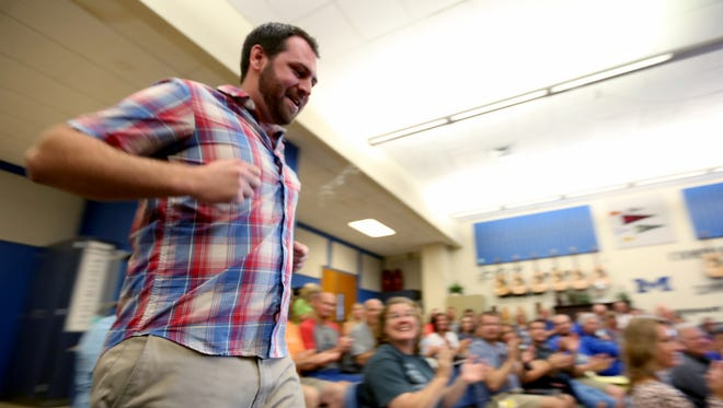 Ben Busch, a new Physical Education teacher, runs through the crowd during a parody new staff draft at McNary High School in Keizer on Tuesday, Aug. 30, 2016. Oregon jobs surged through Sept., spurred by local government education hires.
