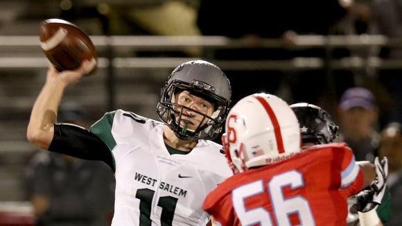 West Salem's Jared Oliver (11) passes the ball past South Salem's J. Dario Hernandez (56) in the first half of the West Salem vs. South Salem football game at South Salem High School on Friday, Oct. 21, 2016. West Salem won the game 45-9.