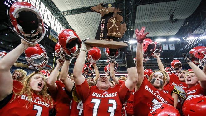 Romeo's Christopher Zanke lifts the Divisin 1 state championship trophy at Ford Field on Nov. 28, 2015.