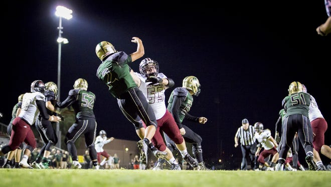 Lineman Manny Roberson (55) of Red Mountain pressures quarterback Tj Duarte (2) of Skyline in the first half of the 6A first-round football playoff game between Red Mountain and Skyline at Skyline High School on Friday, Nov. 4, 2016 in Mesa.