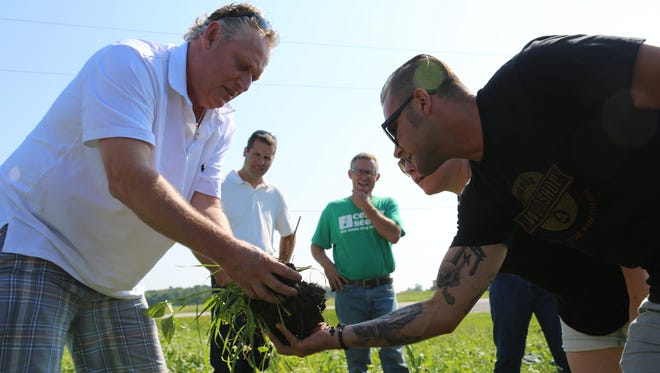 Jeff Rasawehr, left, shows Union Joints Executive Chef Aaron Cozadd what healthy soil looks like on one of his fields near Celina, Ohio. The pair have teamed up with Gino Baratta, a third-generation butcher at Fairway Packing, to produce Cover Crop Ranch meat.