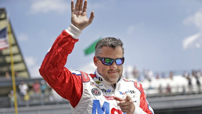 Sprint Cup Series driver Tony Stewart (14) waves to the crowd and points to a photographer before the start of the Brickyard 400, Sunday, July 24, 2016.