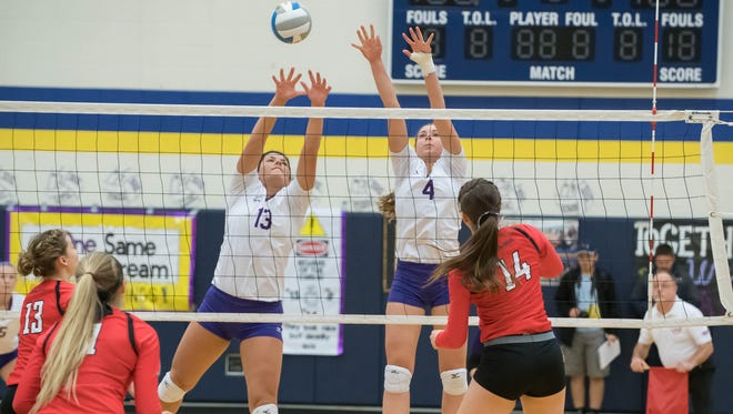 Bronson's Jill Pyles (13) Allison Sikorski (4) go for the block during the MHSAA Quarterfinals against Laingsburg Tuesday evening.