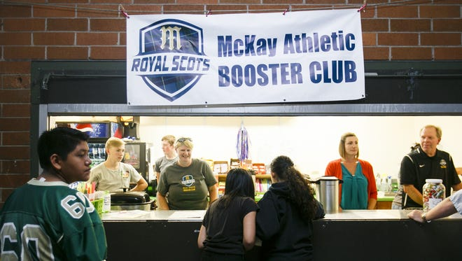 Parents and volunteers with the McKay Athletic Booster Club run the concessions stand at a McKay High School football game on Friday, Sept. 16, 2016.