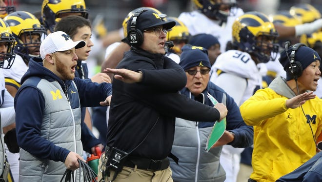 Michigan Wolverines head coach Jim Harbaugh signals that Ohio State was short on fourth-and-1 during the second overtime Saturday, Nov. 26, 2016 at Ohio Stadium.
