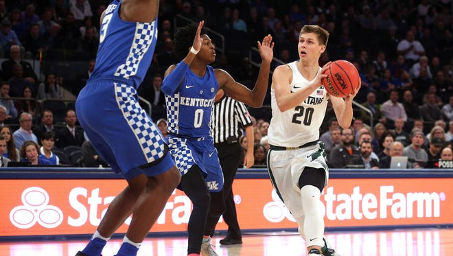 Michigan State guard Matt McQuaid (20) drives against Kentucky guard De'Aaron Fox (0) during the first half Tuesday in New York.