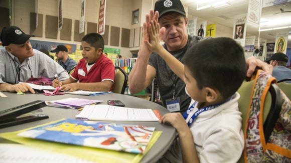 Mike Parker,  CEO and founder of Next Phase Enterprises, gives a high-five to Jose Acosta, 7, after reading a  book and doing science projects at the Dream Center in the Family Dining Hall in December 2016.