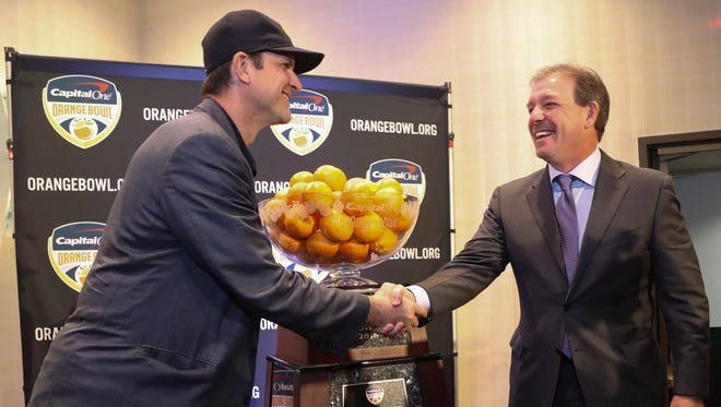 Michigan football coach Jim Harbaugh, left, and Florida State coach Jimbo Fisher pose with the Capital One Orange Bowl trophy Thursday, Dec. 29, 2016, in Fort Lauderdale, Fla.