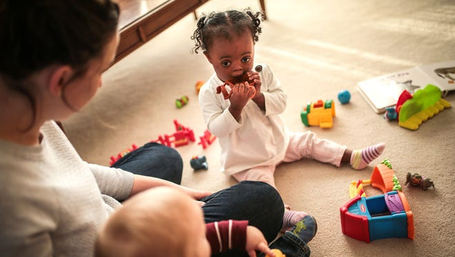 Julia Fenton, 1, of Canton, plays with her brother Daniel Fenton, 1, of Canton, as their mother Katie Fenton, 27, of Canton, watches at home on Tuesday, December 20, 2016 in Canton.