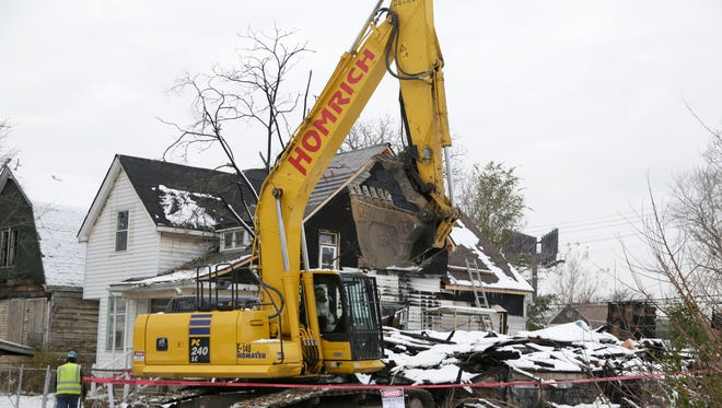 The Detroit Land Bank Authority is a key player in Detroit's blight removal effort, as shown by this demolition of a house on Lyon Street in southwest Detroit in November 2015.