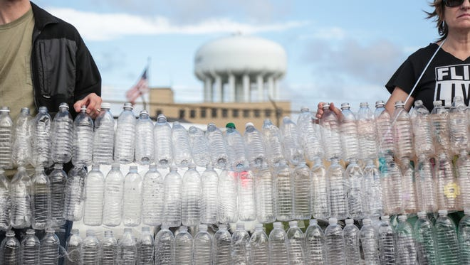 A wall of empty water bottles is held as a backdrop as media films speakers calling out Republican Presidential candidate Donald Trump during a press conference outside of the Flint Water Treatment Plant Wednesday, Sept. 14, 2016, before Trump's visit to Flint.
