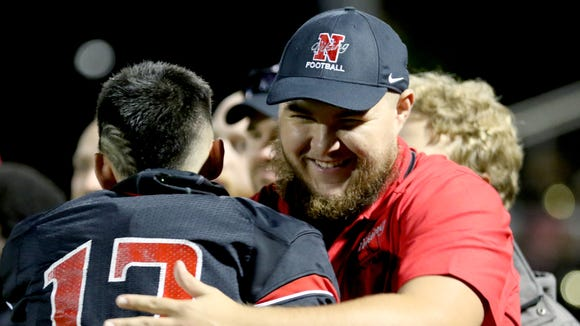 Chris Feskens, a North Salem graduate and current Willamette University offensive lineman, hugs a senior player on Senior Night while acting as a volunteer assistant coach for North Salem before their final regular season home game against McKay at North Salem High School on Friday, Oct. 21, 2016.