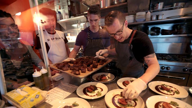 Chef James Rigato of Mabel Gray restaurant in Hazel Park  plates the main course dish with Dry aged beef, red and green harissa, beef fat potatoes, tonm, during theTop 10 take over on Monday, June 13, 2016.