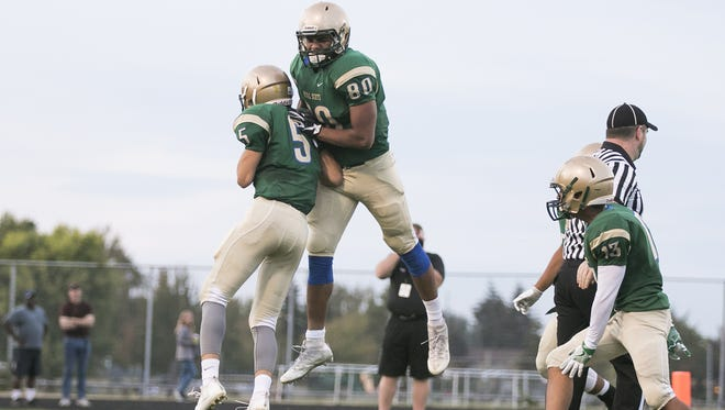 McKay's Jamer Silva (80) jumps up with teammate Cyrus Mora (5) to celebrate a touchdown in a game against Forest Grove on Friday, Sept. 16, 2016. The McKay Royal Scots won the game 43-0.