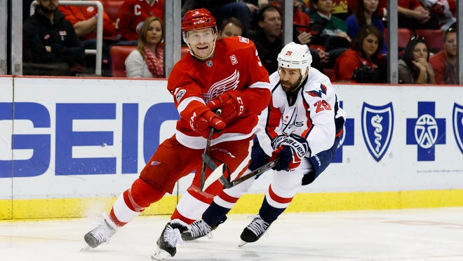 Detroit Red Wings defenseman Nick Jensen, left, passes the puck against the Washington Capitals on Feb. 18, 2017.