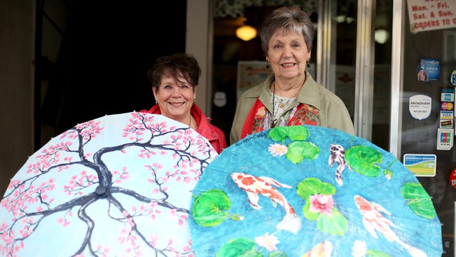 Lorraine Dye, left, and Linda Sunderland, show off hand-painted parasols that will be available for purchase during the Cherry Blossom Festival outside the Oregon State Capitol on Saturday, March 18, 2017.